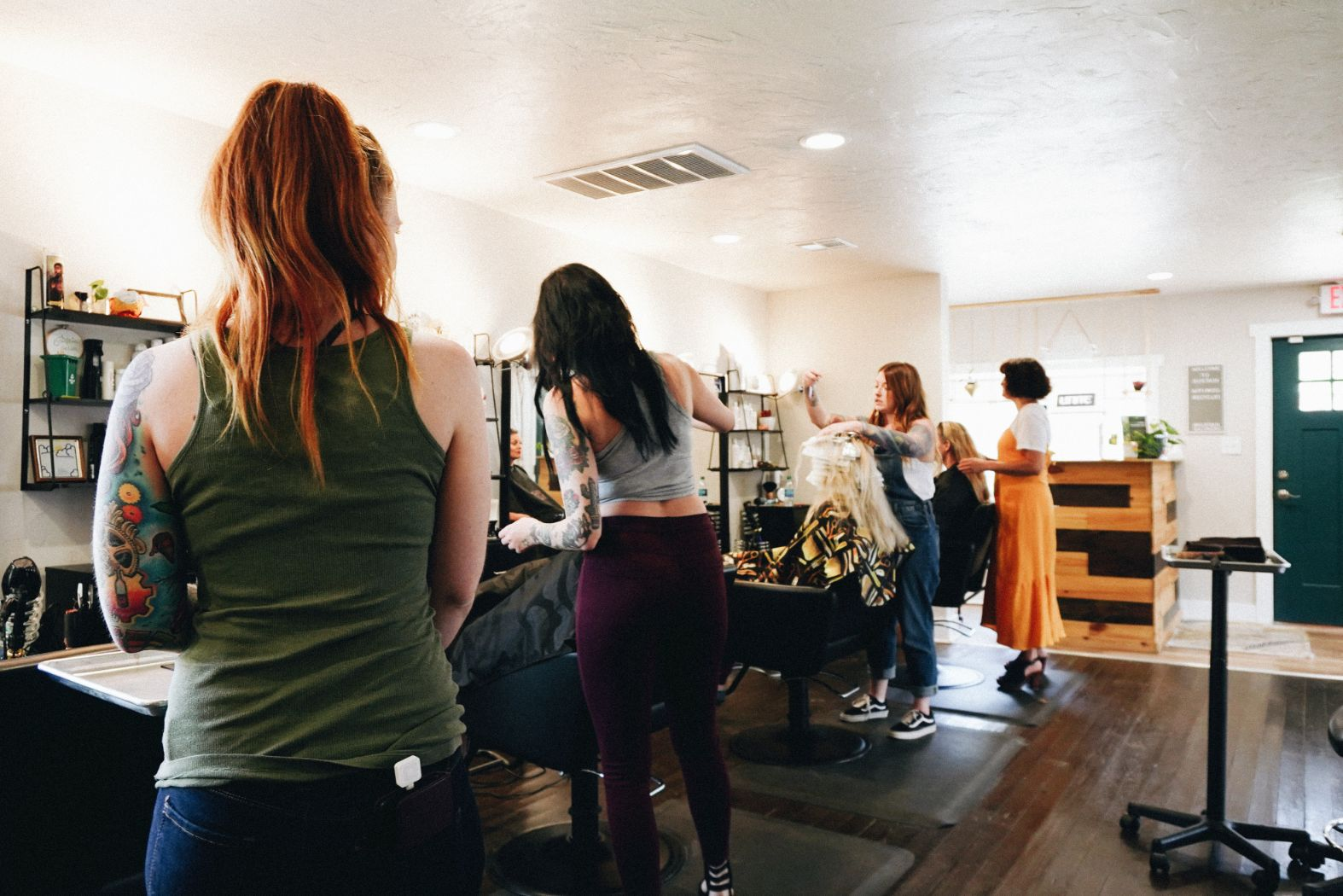 A photograph of the Sustain Salon team in action styling and cutting hair