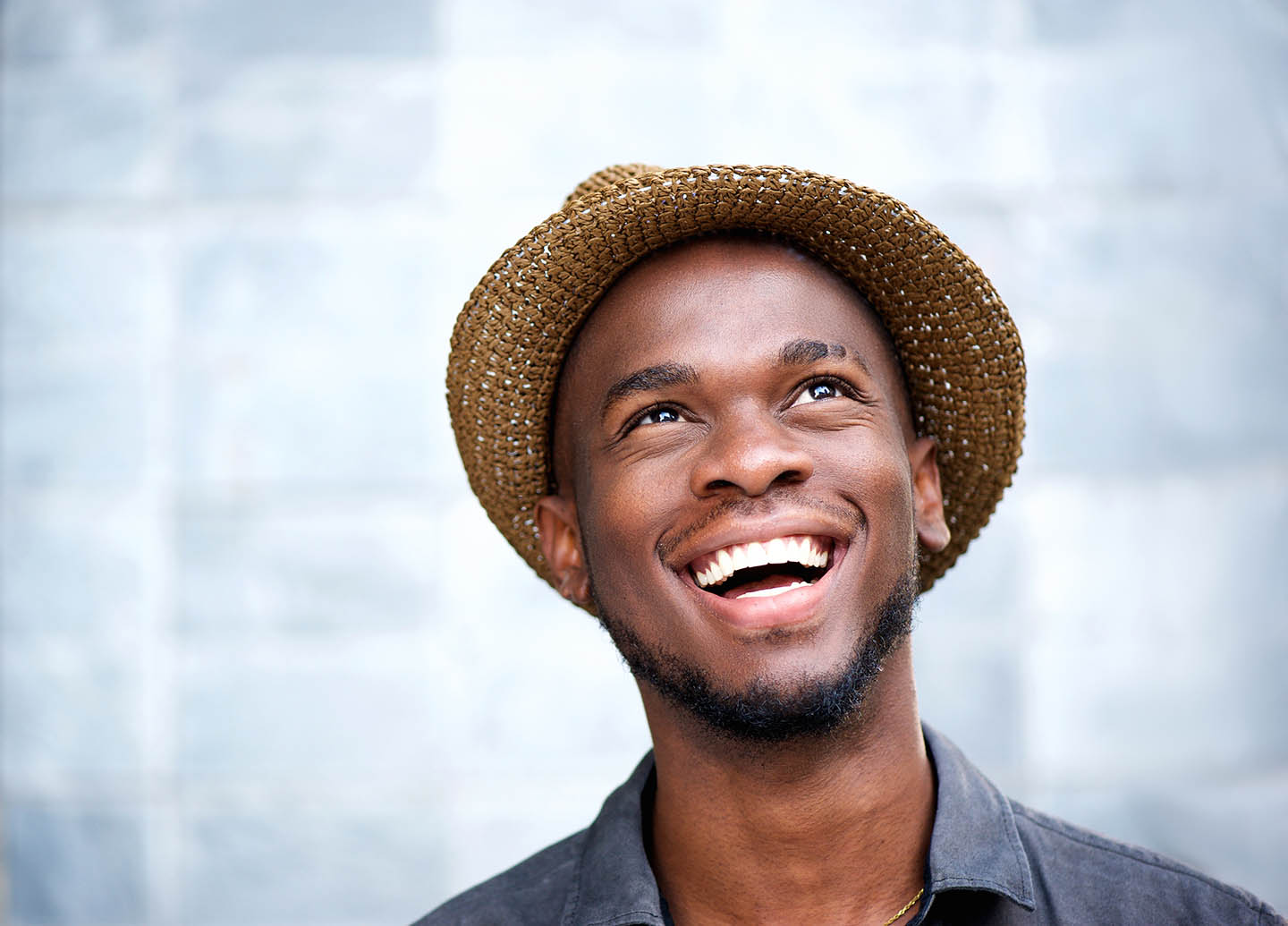 Man in a hat smiling upwards