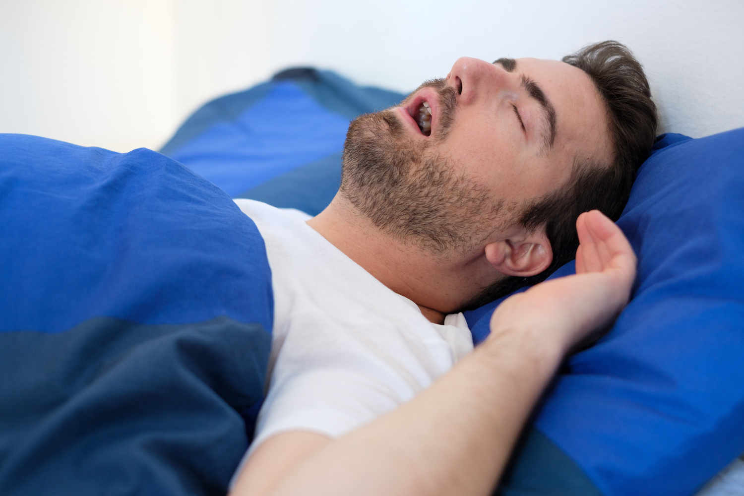 Man snoring loudly in bed