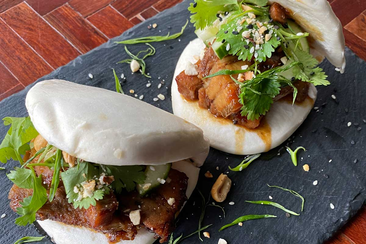 Pork belly bao - soya and honey glazed pork belly with pickled cucumber, coriander, spring onion, sesame seeds and roasted nuts