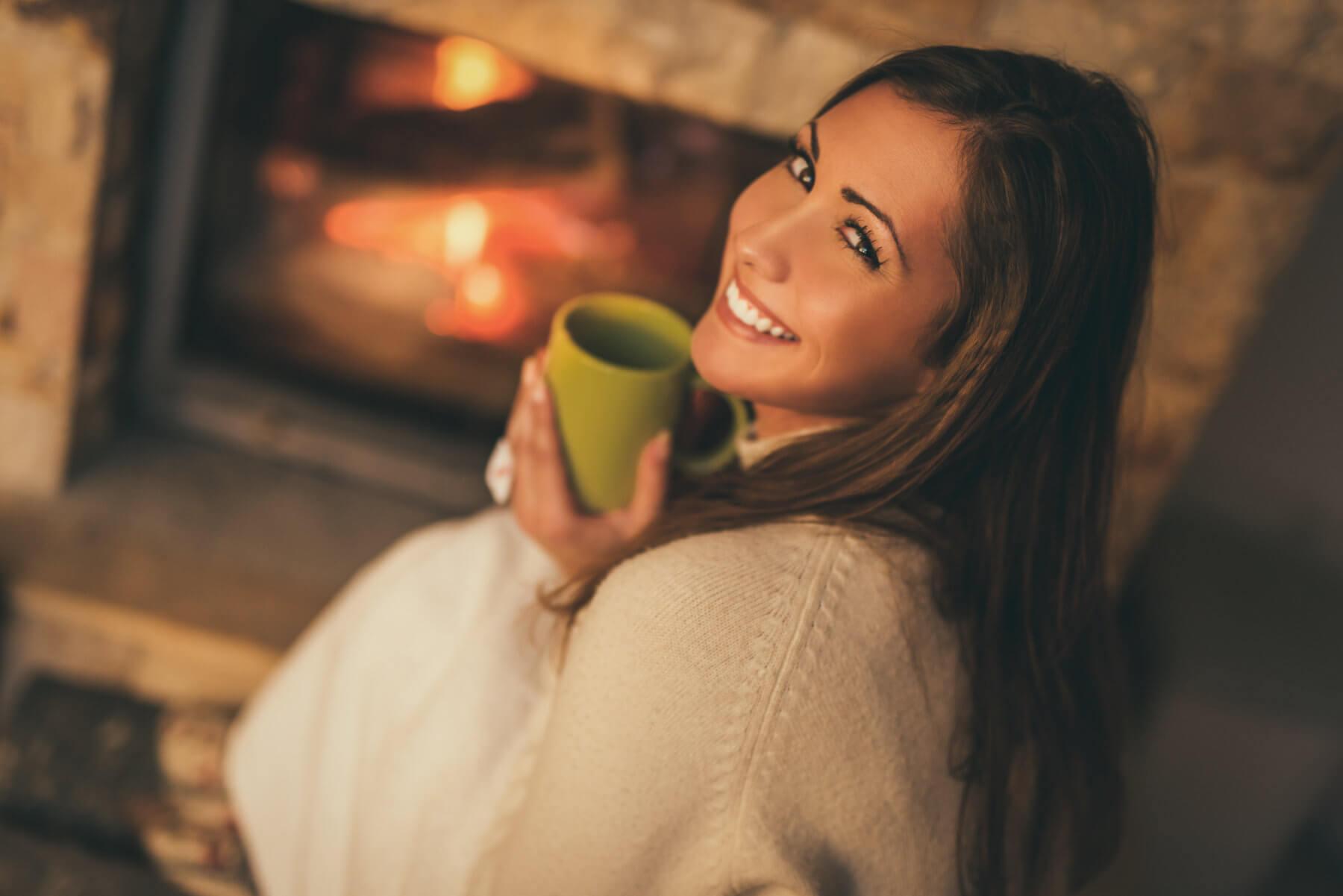 Happy woman near fireplace - jacksonville