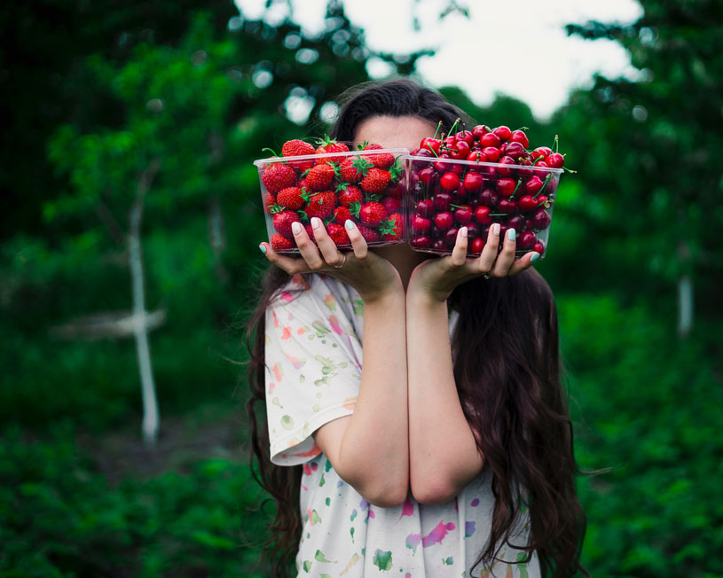Woman holding boxes of strawberries and cherries