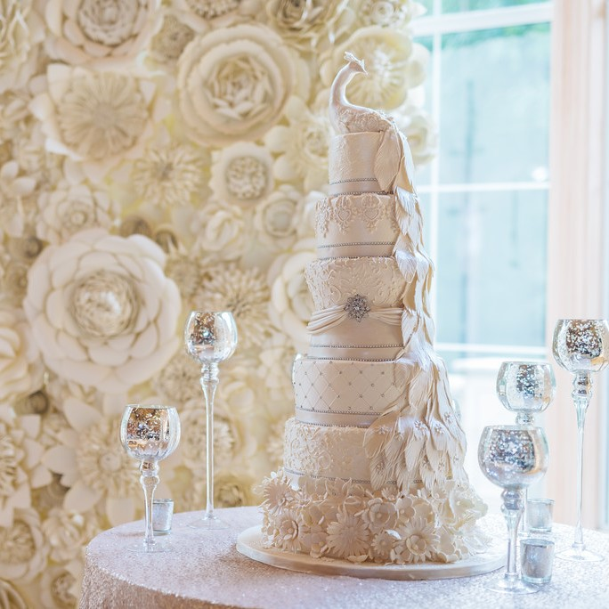 The bride and groom's five tier wedding cake in front of a floral wall.