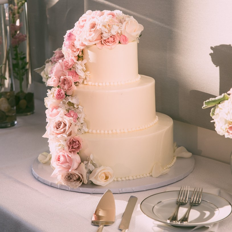The couples wedding cake with cascading flowers.