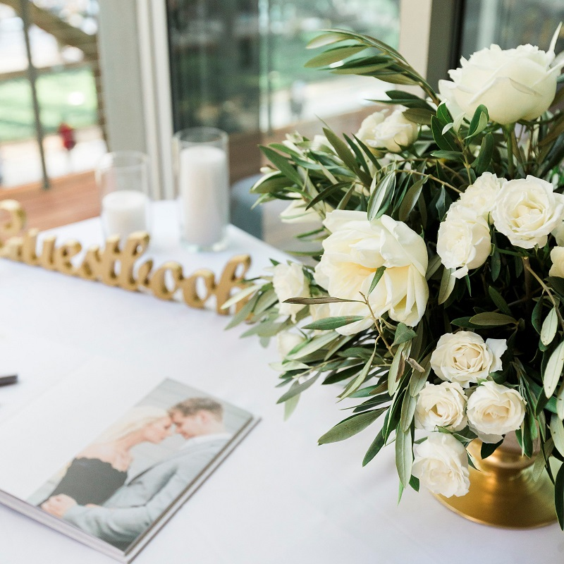 Sign-in table details and wedding centerpiece floral.