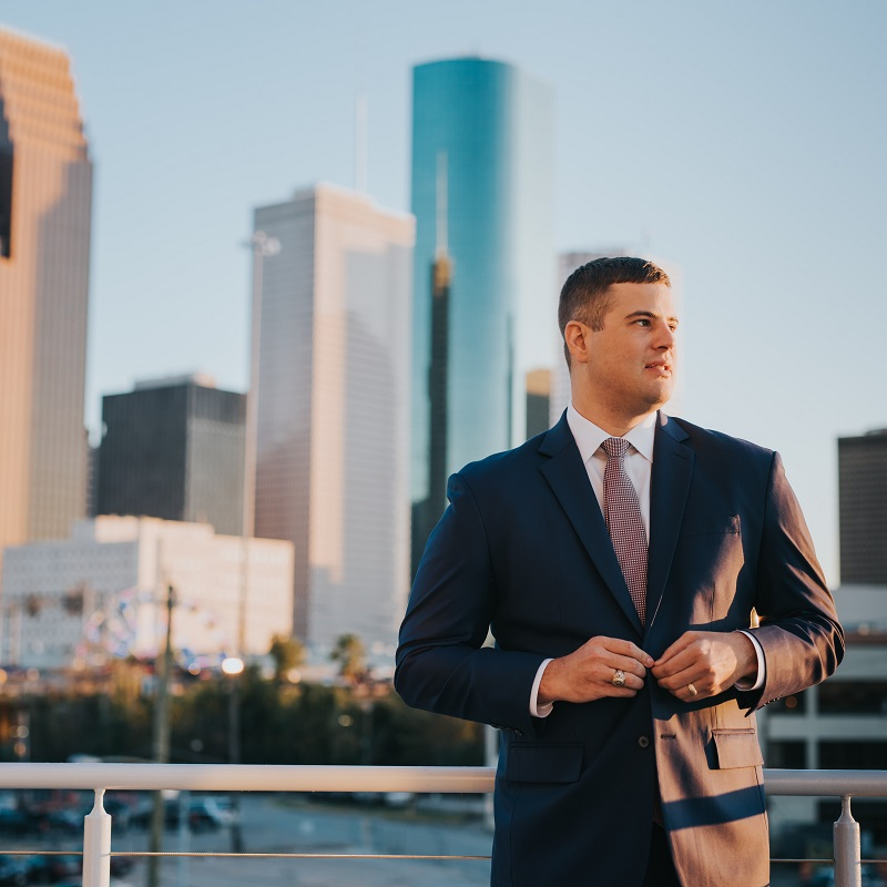 The groom standing in front of downtown Houston.
