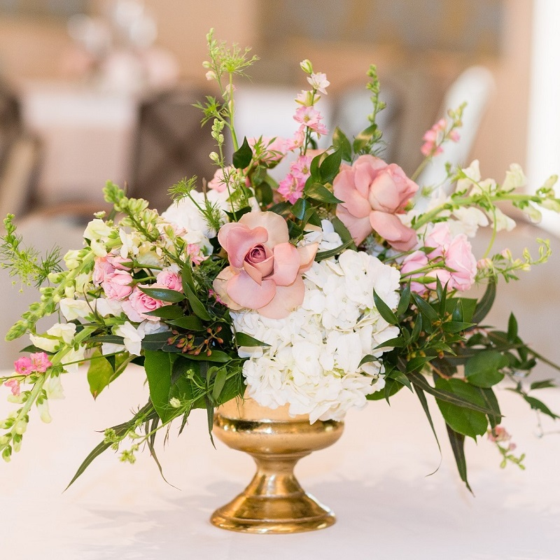 Blush and Ivory wedding centerpiece with greenery in a gold compote vase.