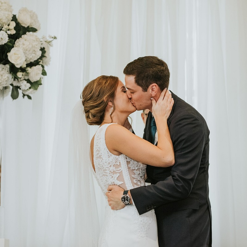 The bride and groom kissing during their ceremony.