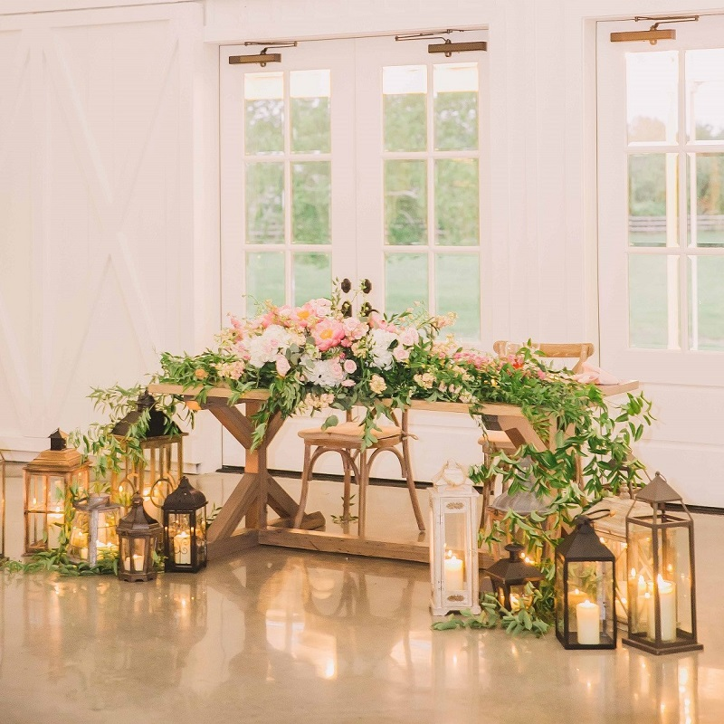 The sweetheart farmhouse table with greenery garland and romantic lanterns.