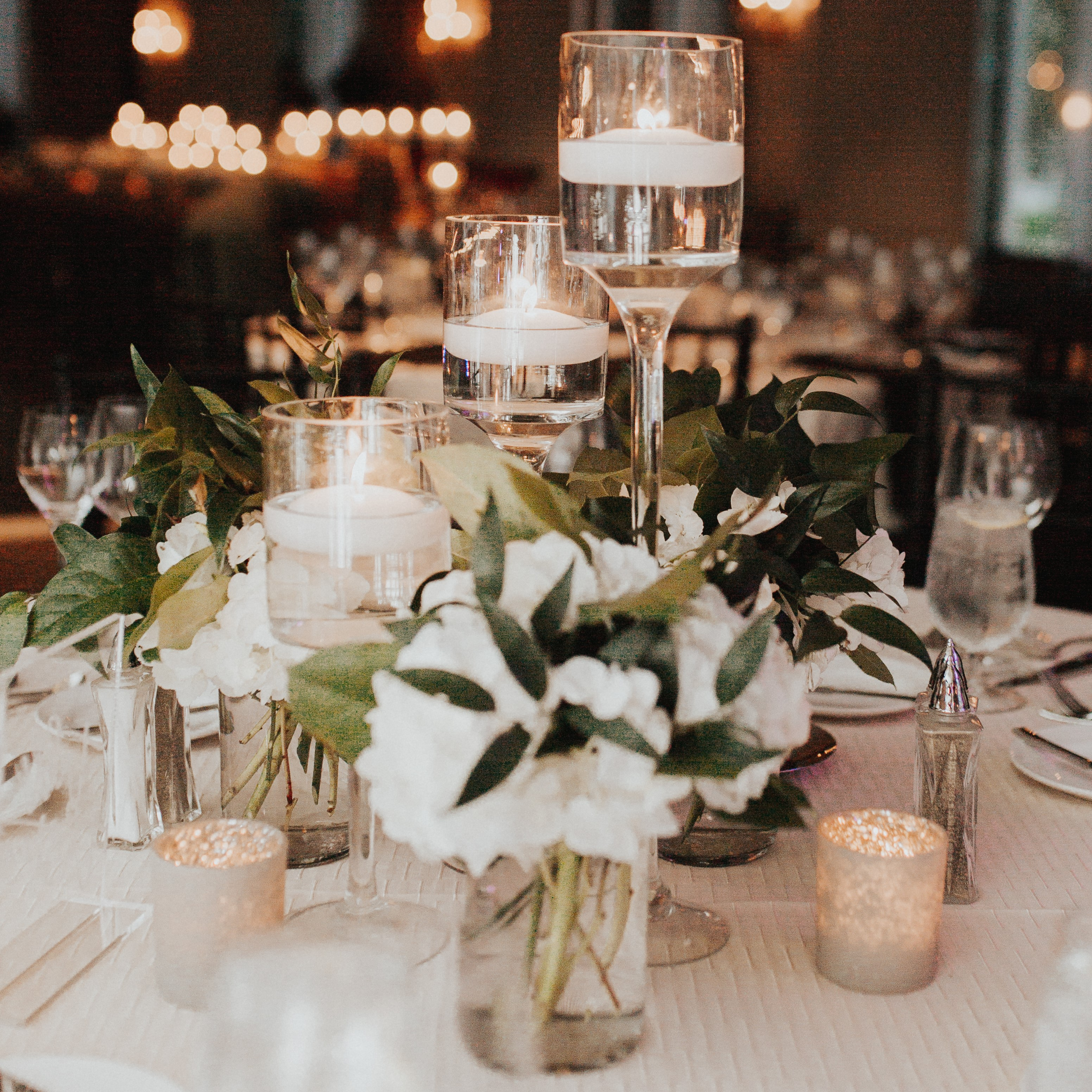 The wedding centerpiece with ivory floral and touches of greenery.