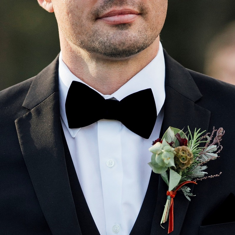 The groom with his velvet bowtie and boutonniere.