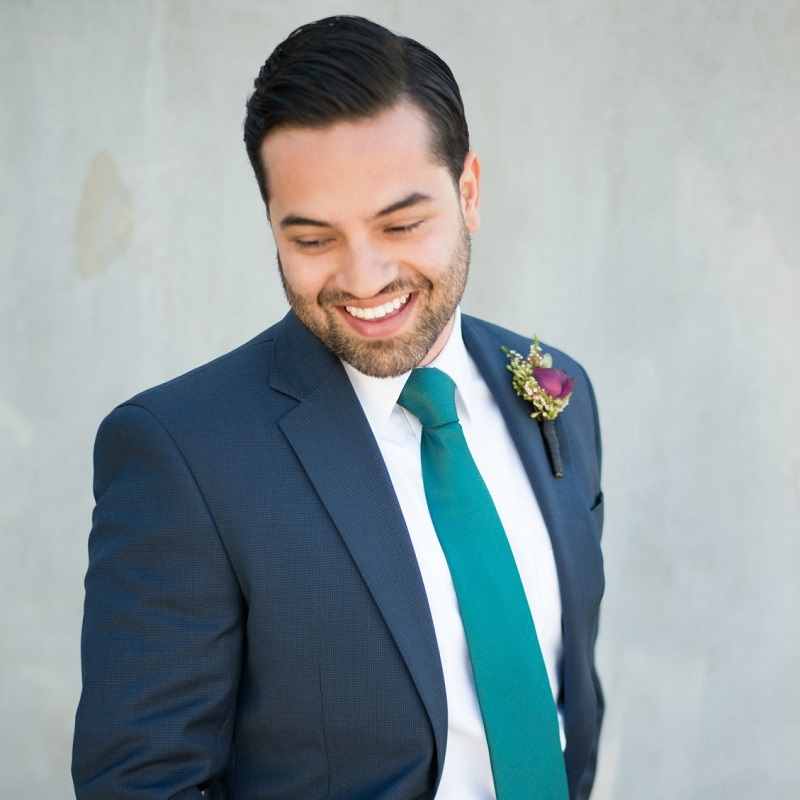 The groom in a navy suit and deep teal tie.