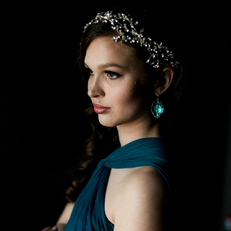 The bridesmaid in a deep teal dress with stunning earrings and jewelry head piece.