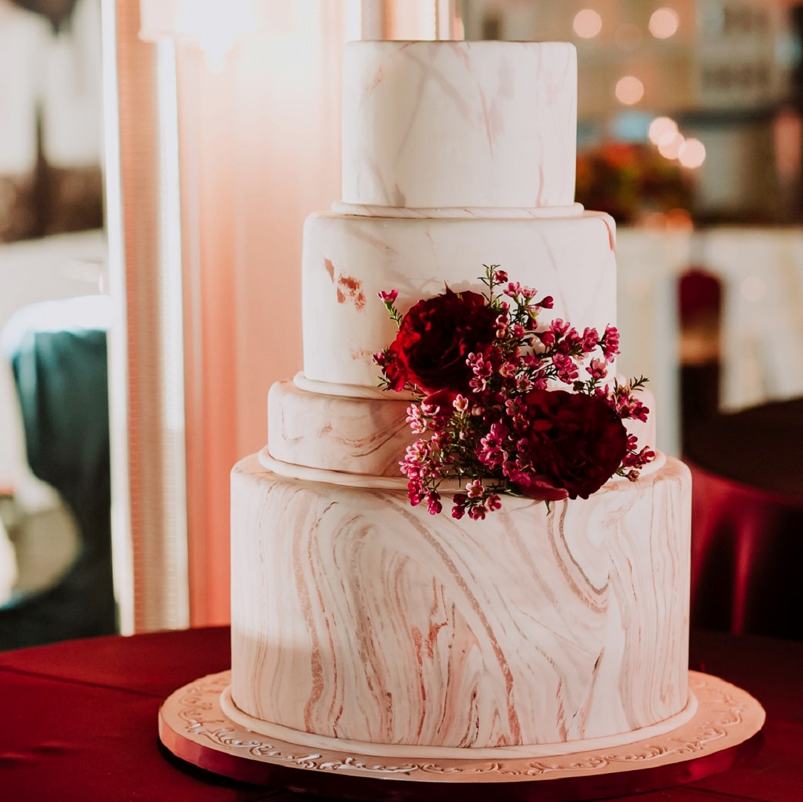 Model wedding cake with burgundy details.