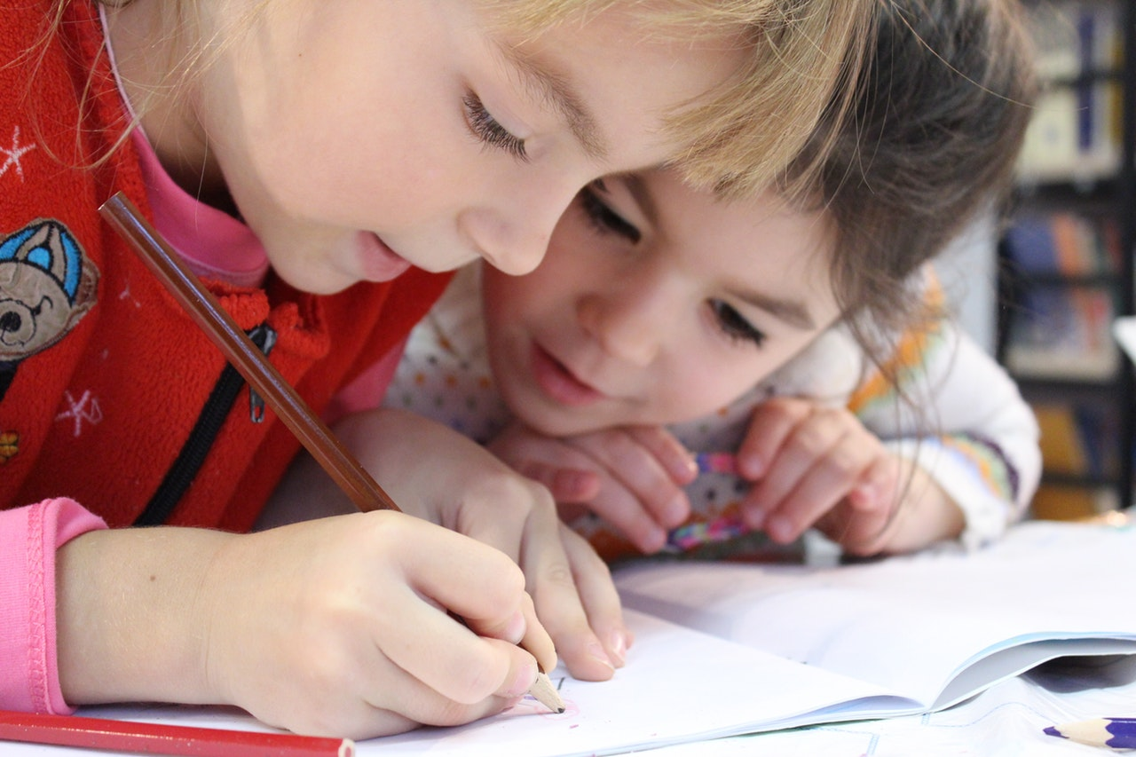 A little girl in a read sweater leans over a notebook, writing. Her friend leans over to see what she's writing.