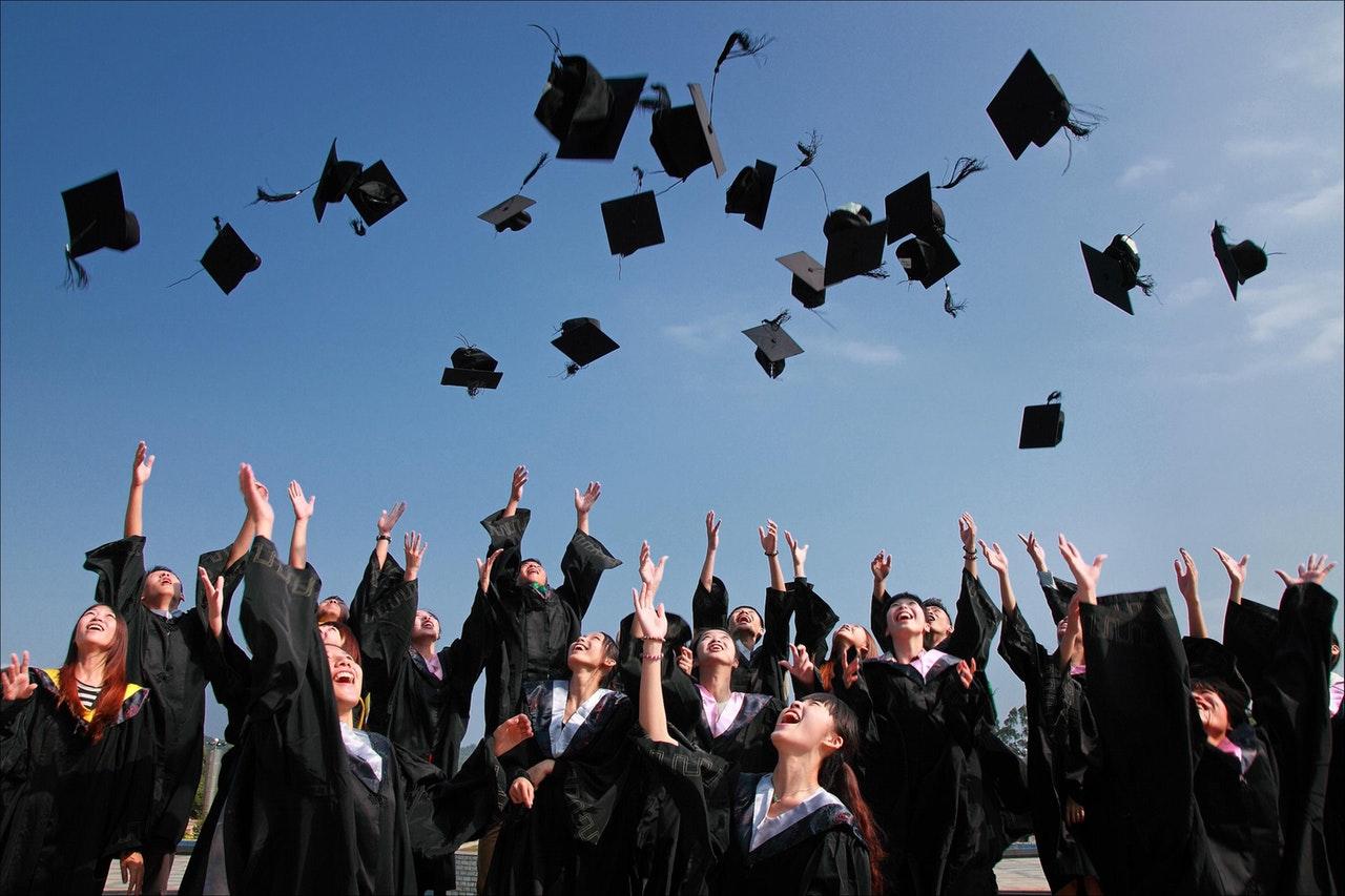 Graduates throw their graduation caps in the air against a bright blue sky.