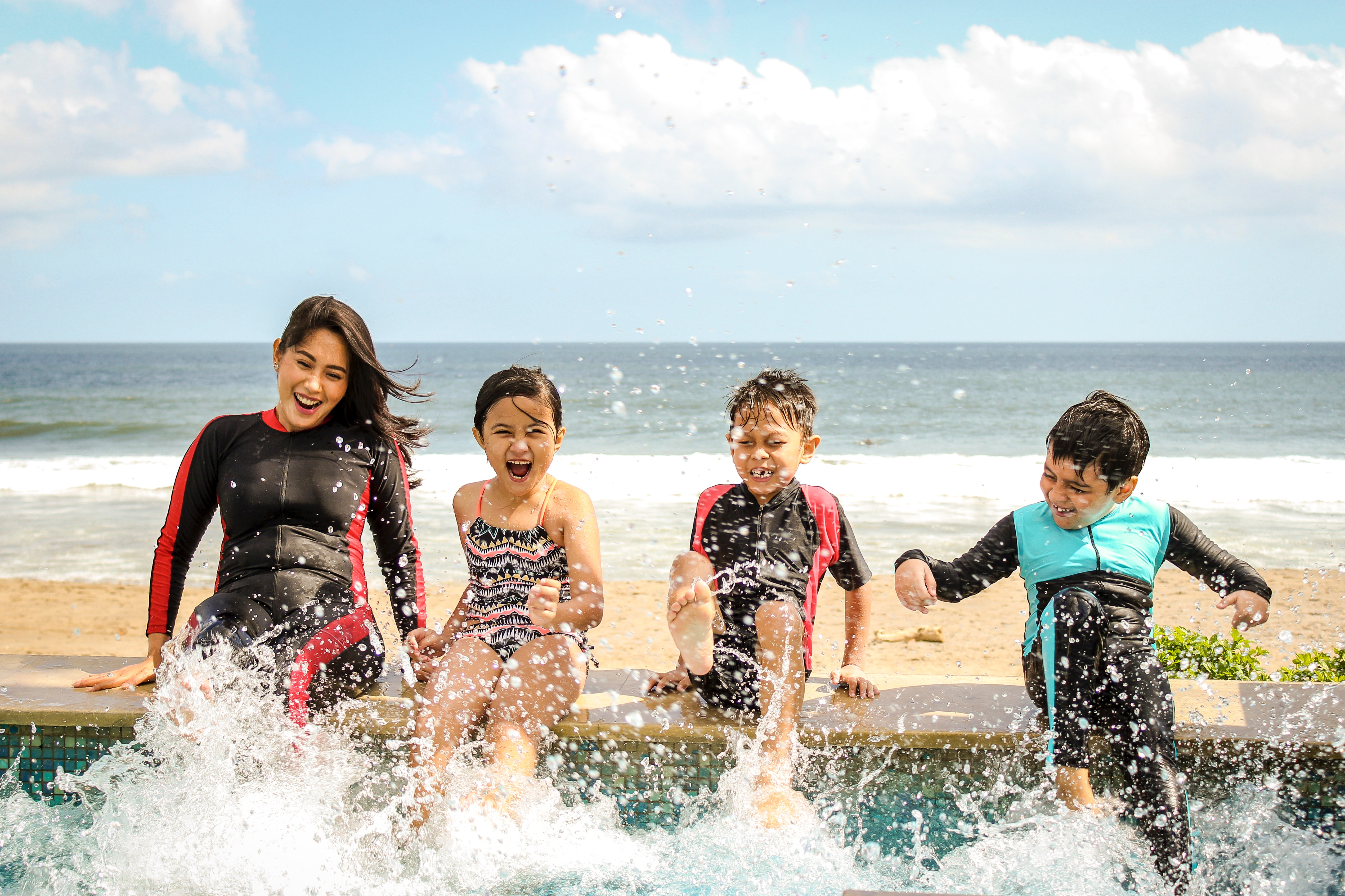 A woman and there children sit at the edge of a beachfront pool, splashing their legs in the pool water.