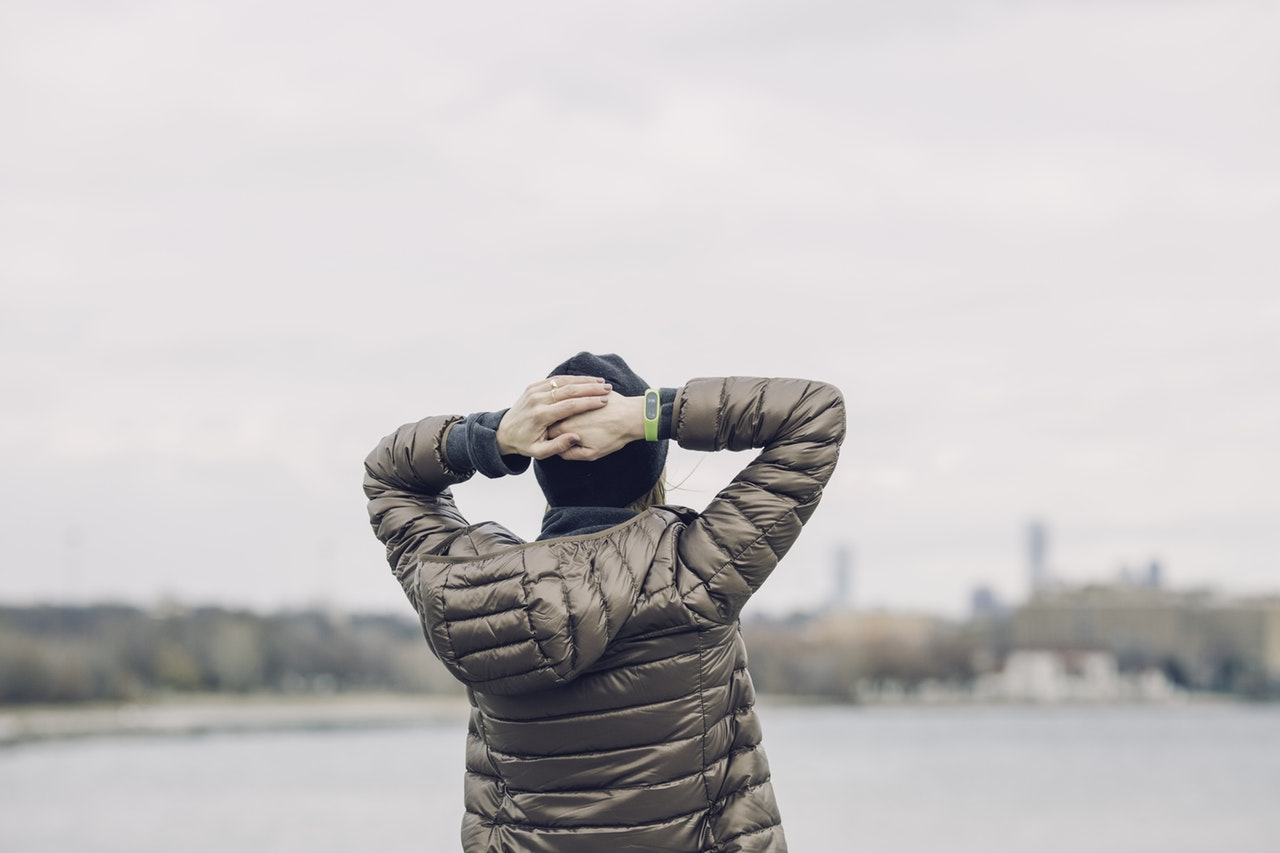 a man in a brown puffer jacket stands gazing out over a lake, his hands placed behind his head in a gesture of exasperation