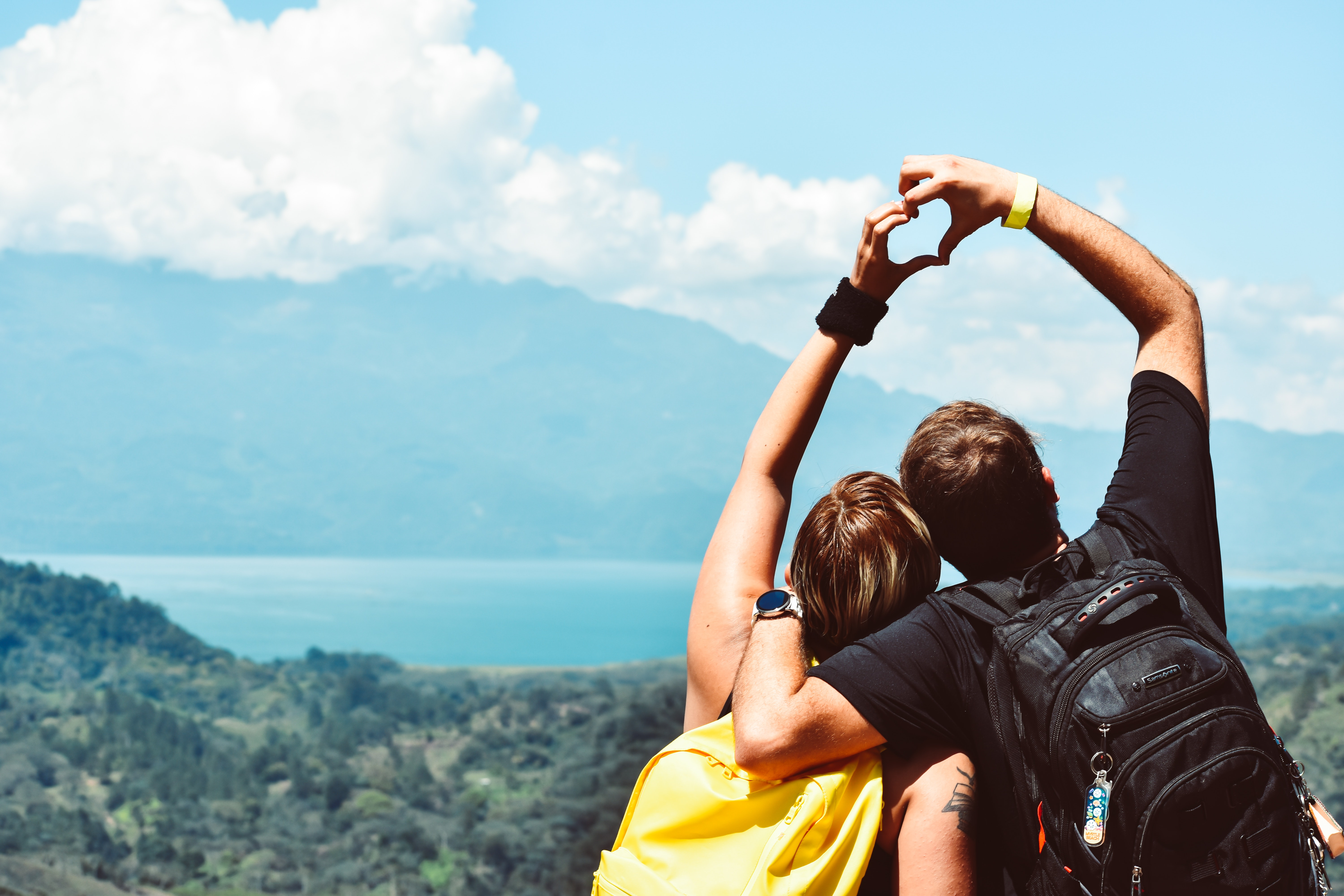 Couple making a heart with their hands on a mountain