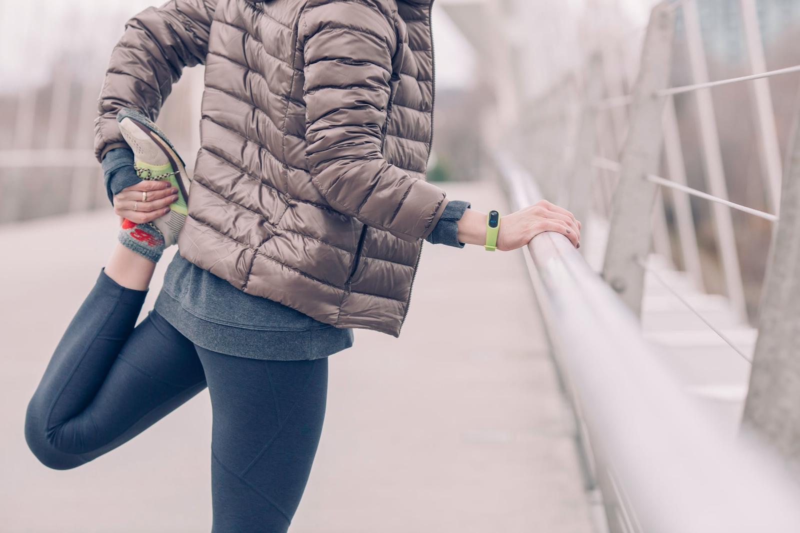 Runner stretching on a bridge in winter gear