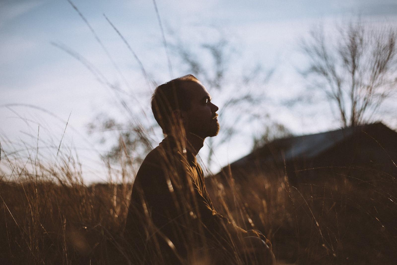 man meditating in a field of grass