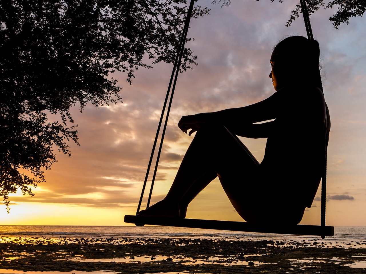 A woman sits on a swing watching a sunset