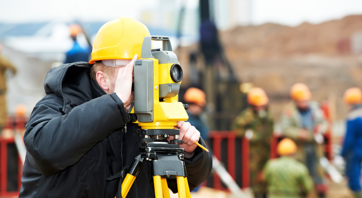 A landscape engineer is using a tool to survey the landscpae