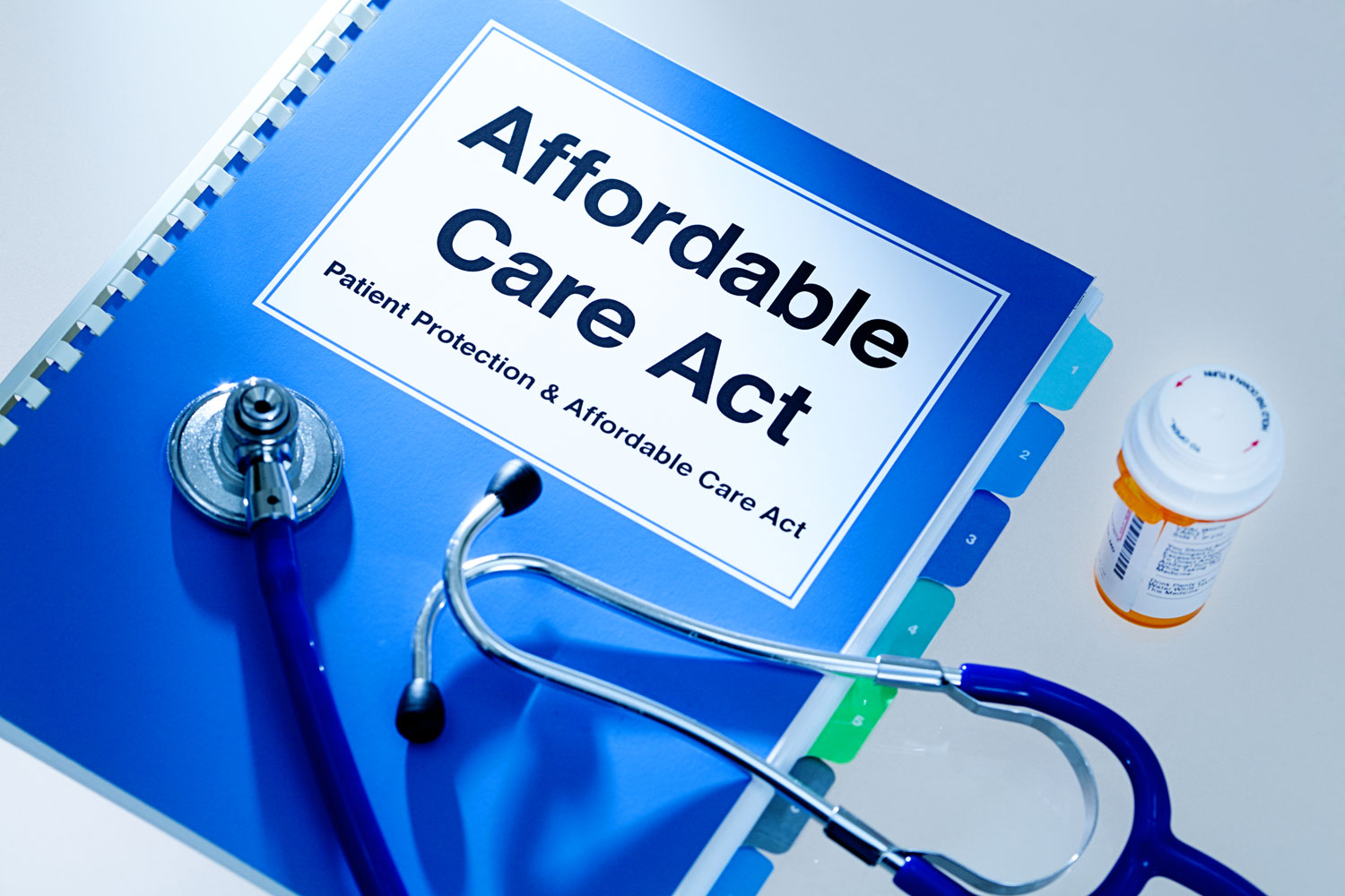 """Blue book that says """"Affordable Care Act"""" with a stethoscope and pill bottle"""