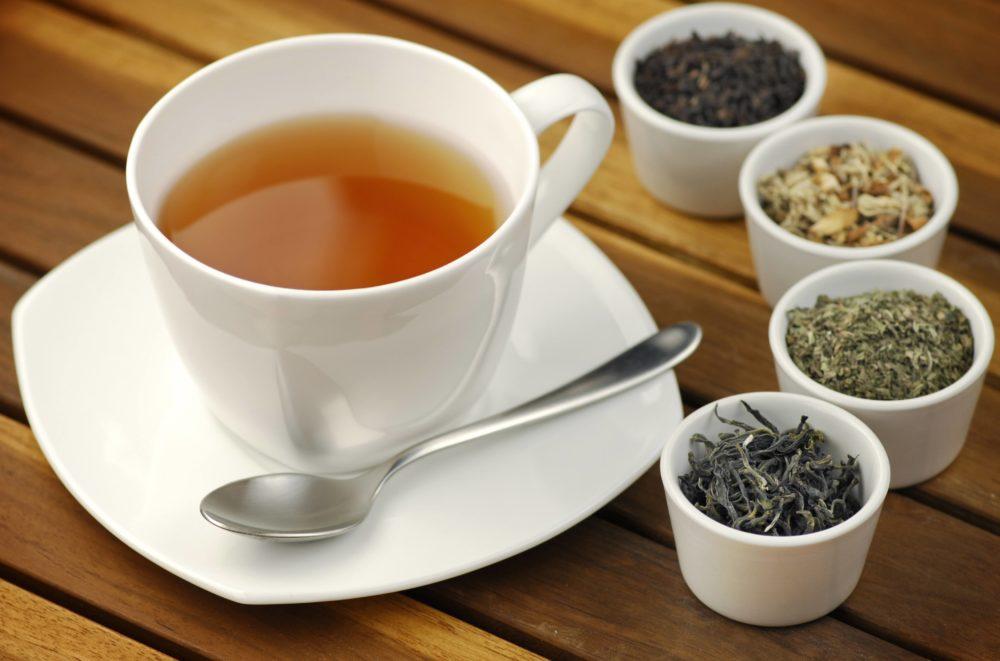 Green tea, black tea, detox tea, white tea cup with a spoon and on a plate