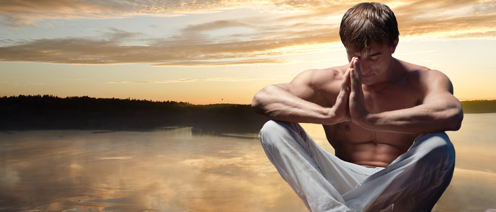 A shirtless man sitting and meditating in with a lake behind him