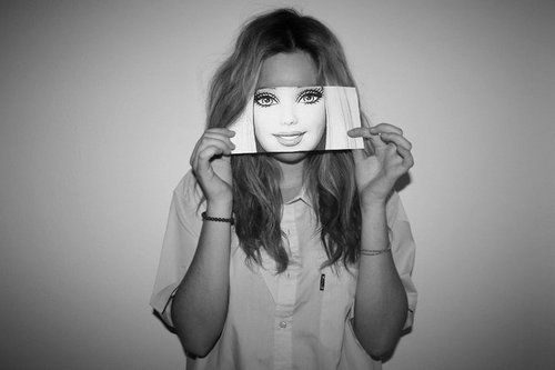 A black and white photograph of a woman holding a print out of a Barbie doll's face in front of her own to indicate the beauty expectations placed on people.