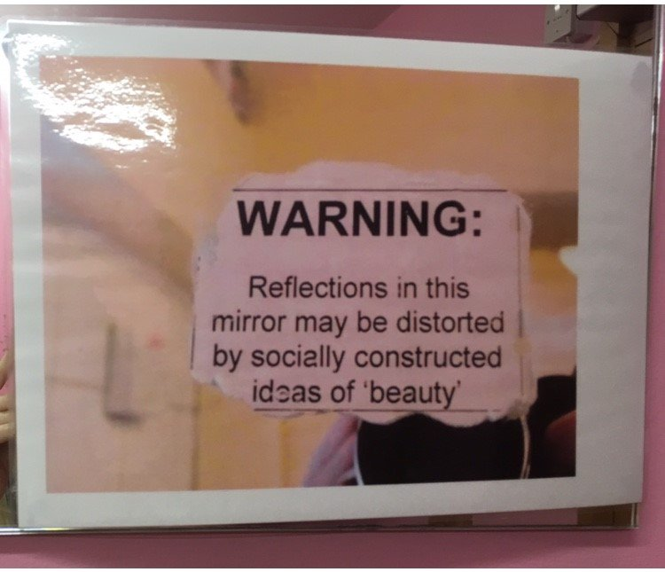 a clipping of a paper that says Warning: reflections in this mirror may be distorted by socially constructed ideas of 'beauty' taped in front of a mirror in which someone is taking a selfie.