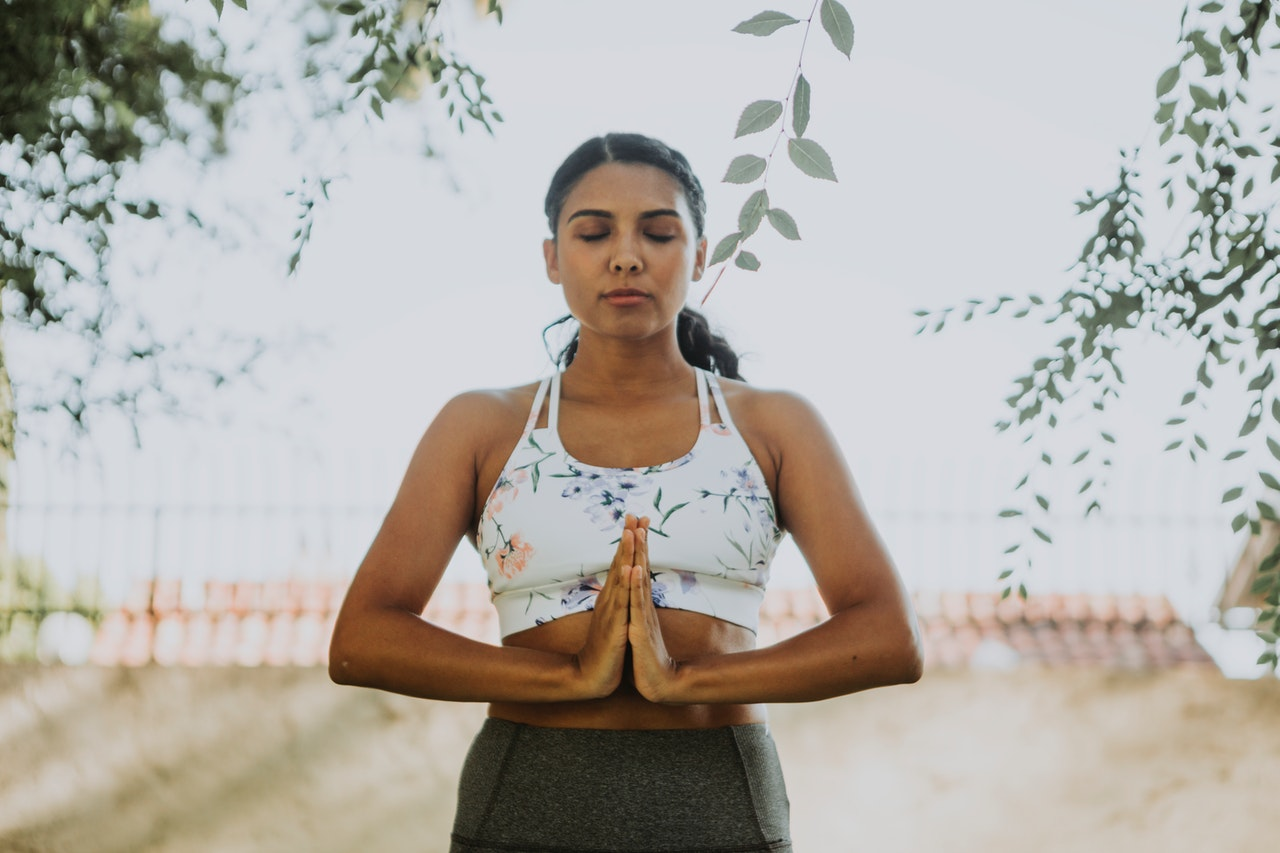 a woman in athletic clothing stands with her eyes closed and her hands pressed together in front of her chest as she meditates