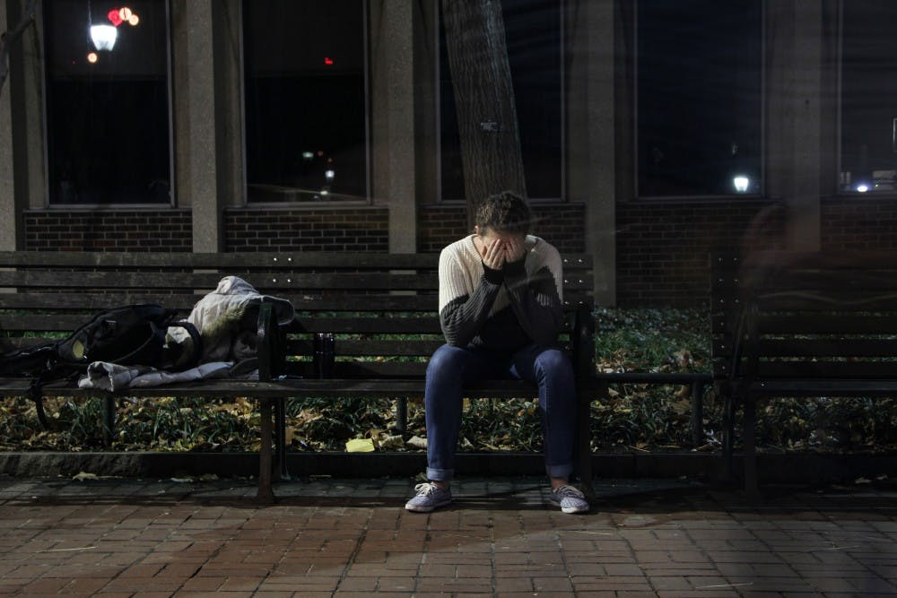 a person on a bench slouches with their head in their hands in a fit of despair