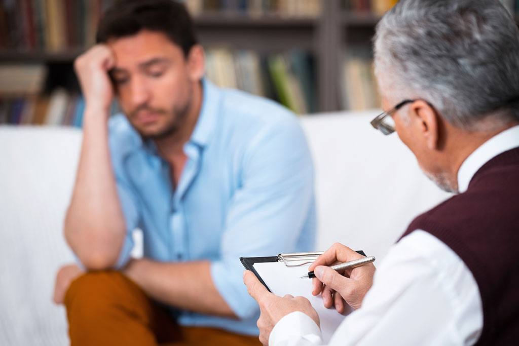 a therapist speaks to a man on a white couch about depression