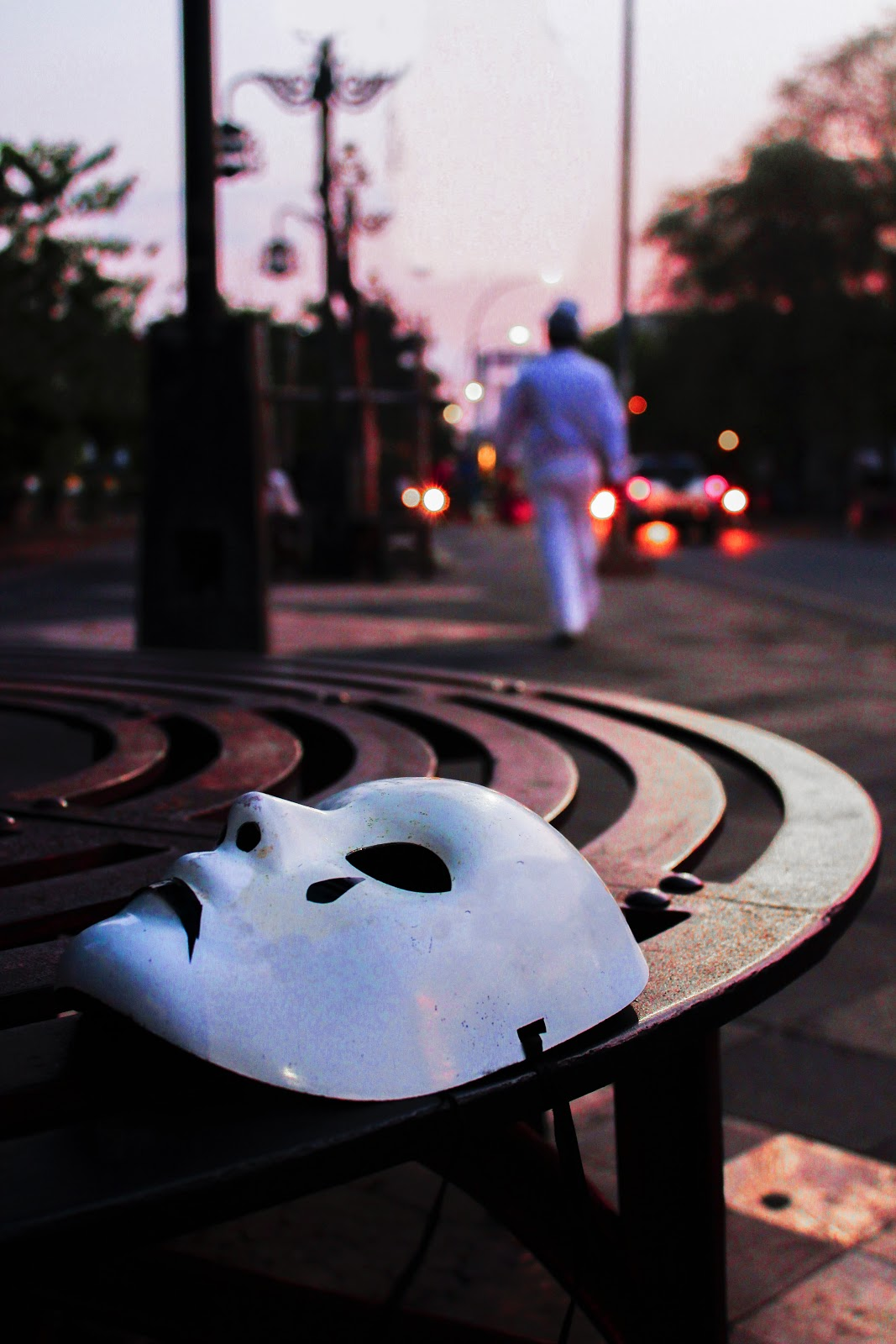 A white mask with teardrops painted on it lying on the ground and facing the sky.