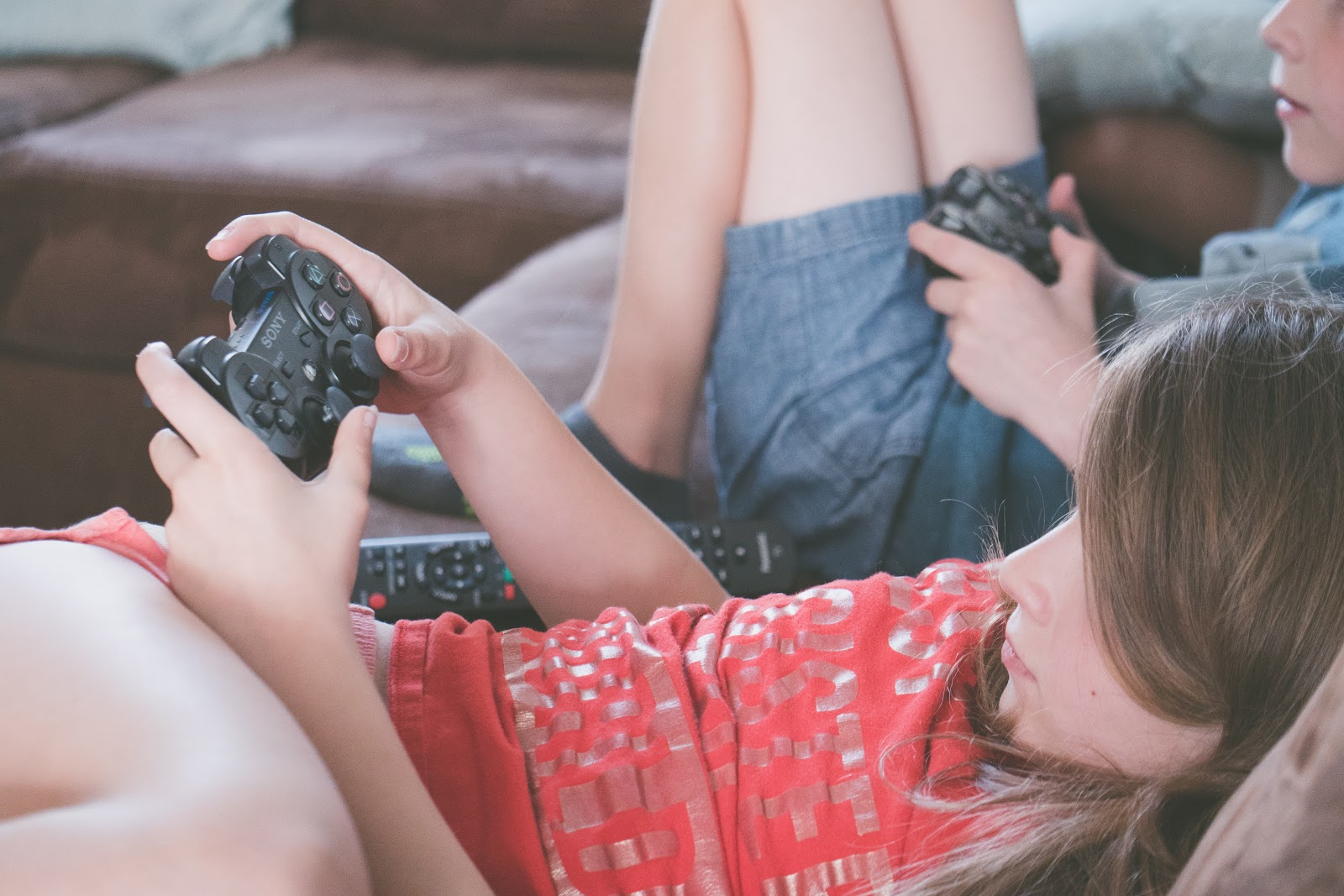 Two kids lounging on a sofa holding game controllers.