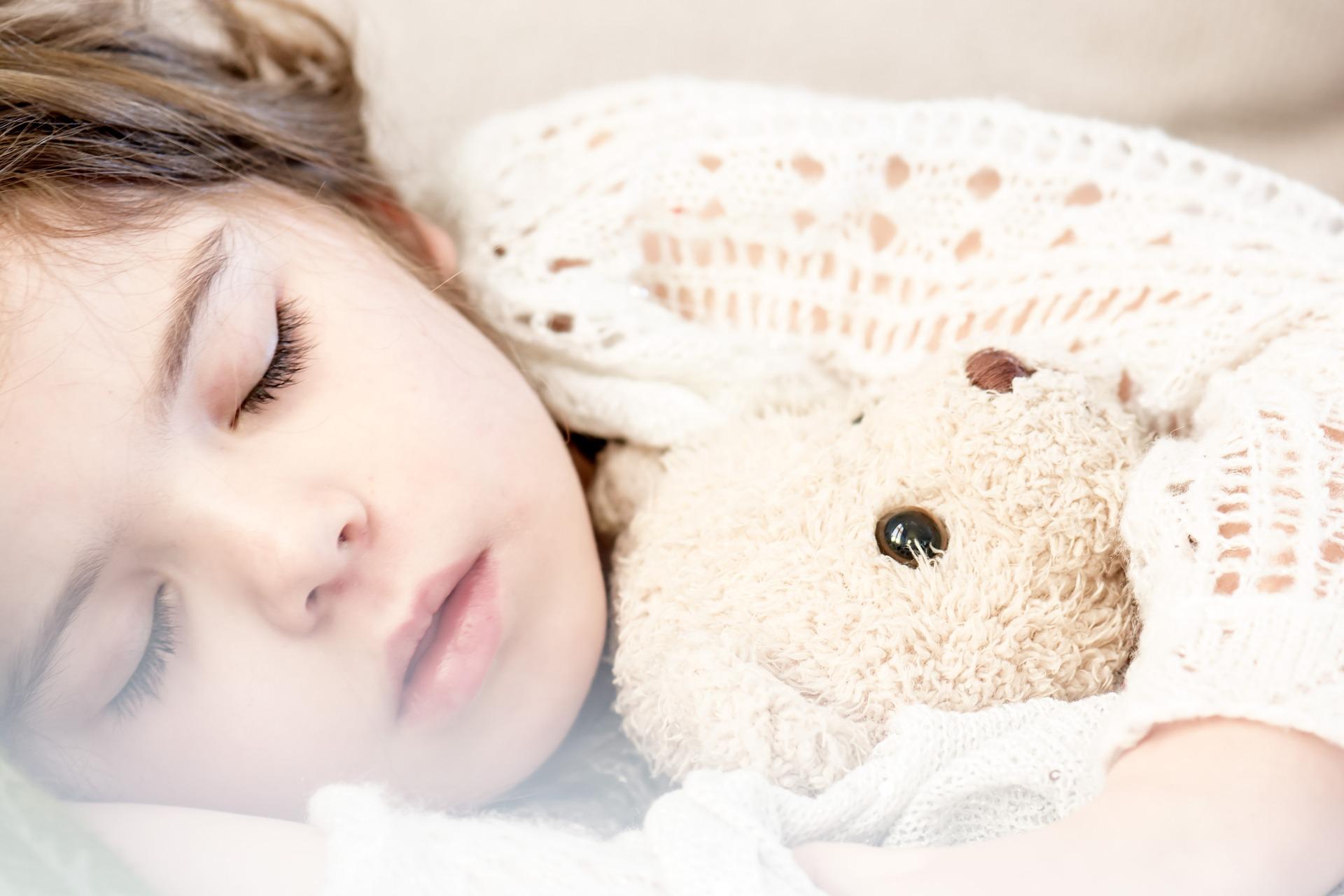 A child holding a teddy bear and sleeping.