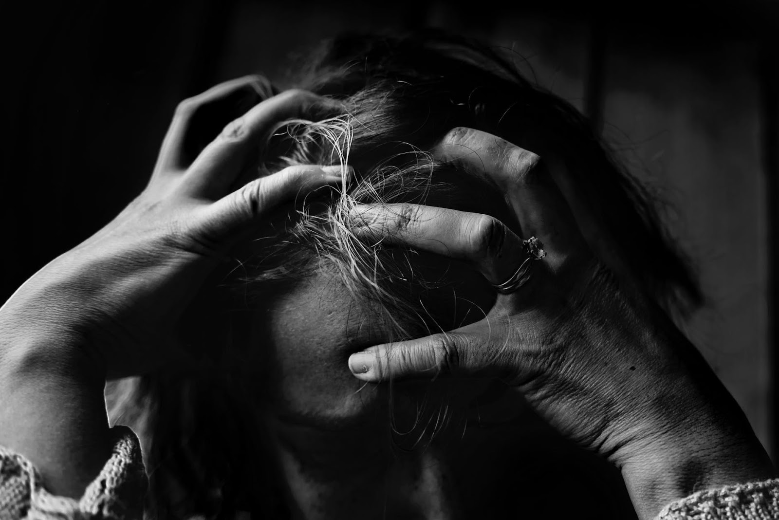 A woman is clutching her head out of frustration from her stressful relationship.