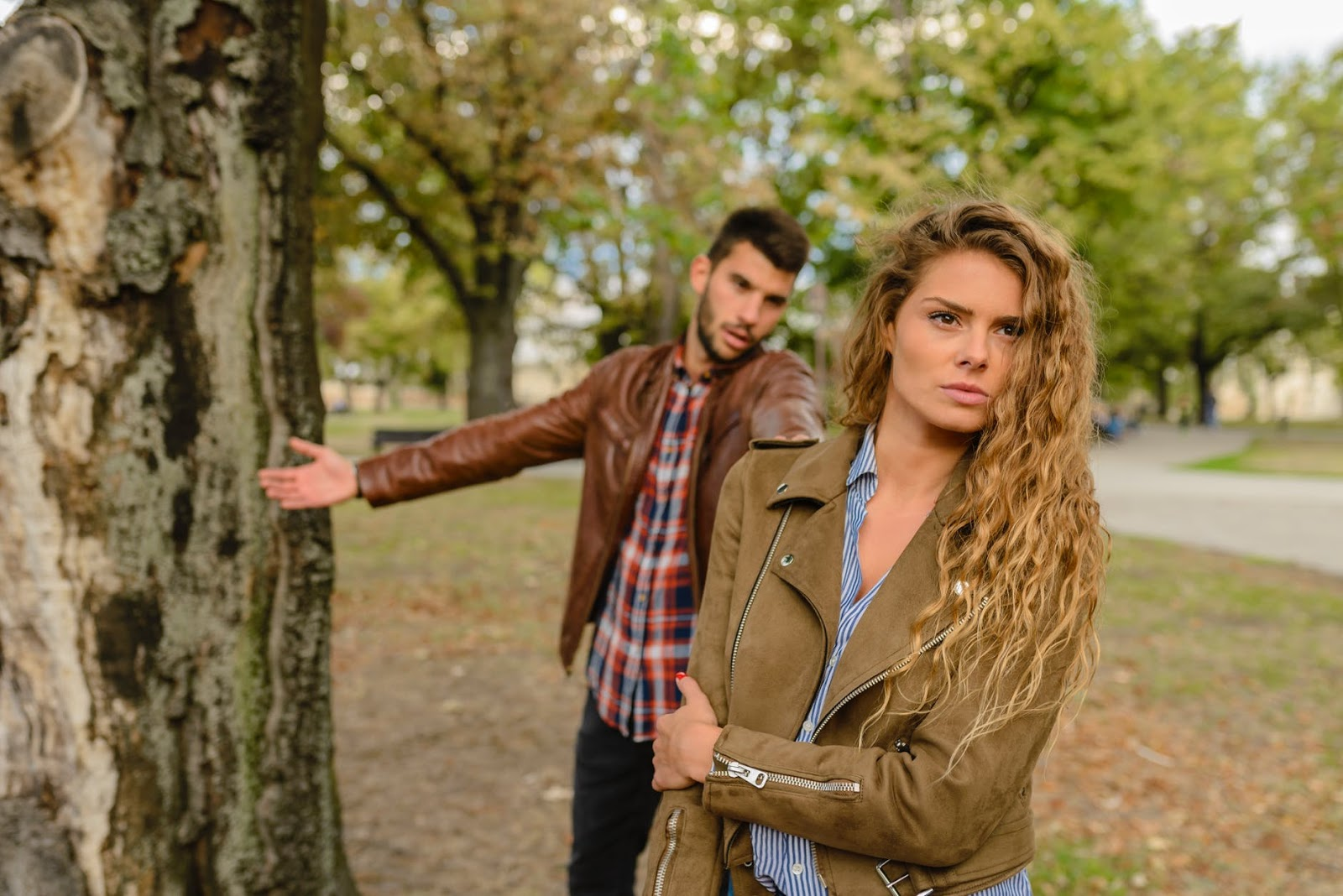 A man and a woman stand by a tree in the park while in a confrontation