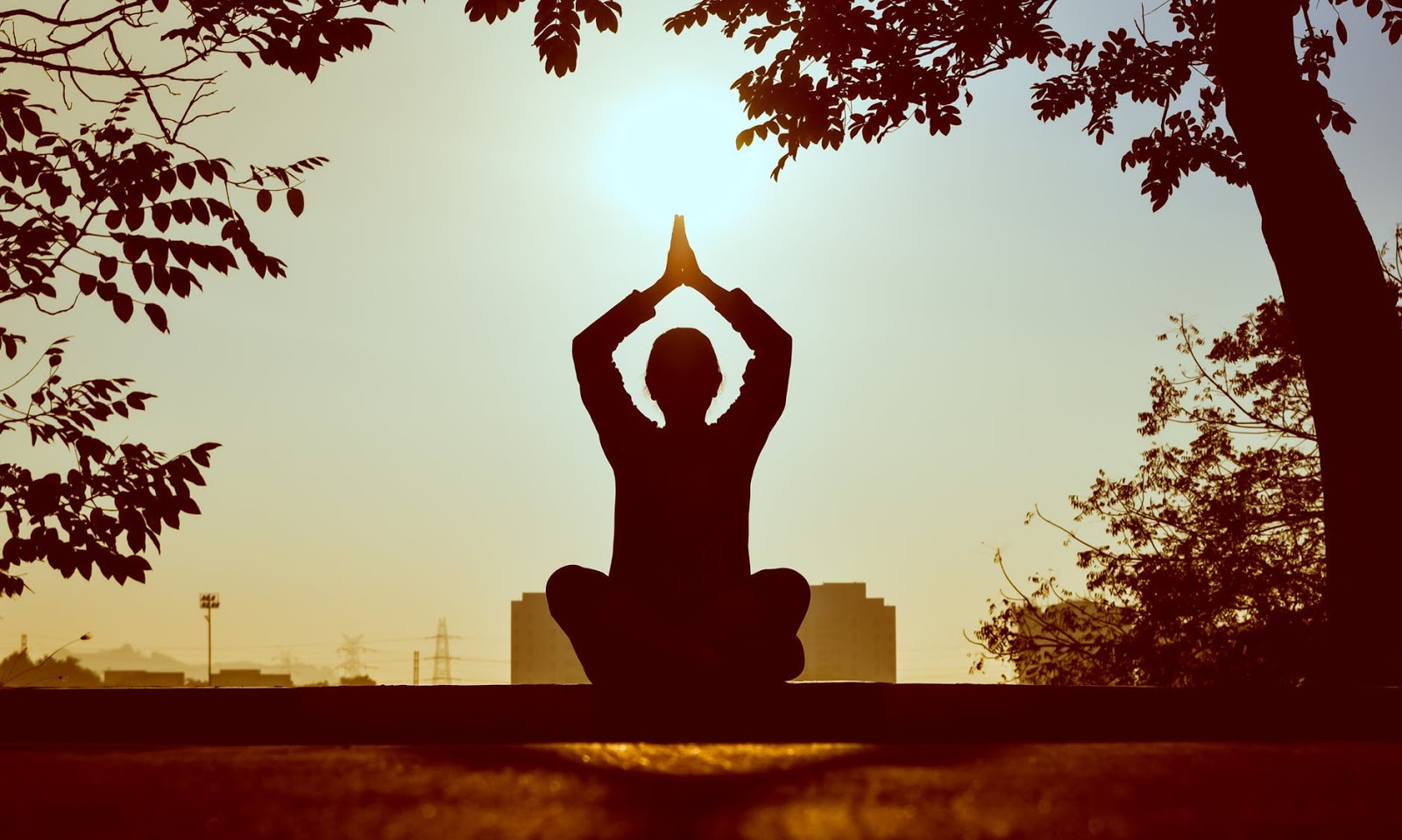 A woman sits in a meditative pose outdoors and facing towards the sun.