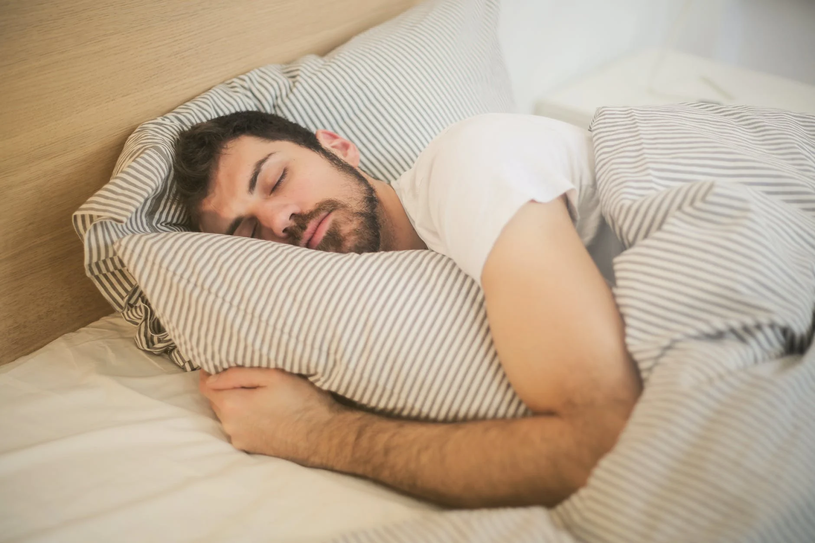 A man sleeps soundly in bed while hugging a pillow