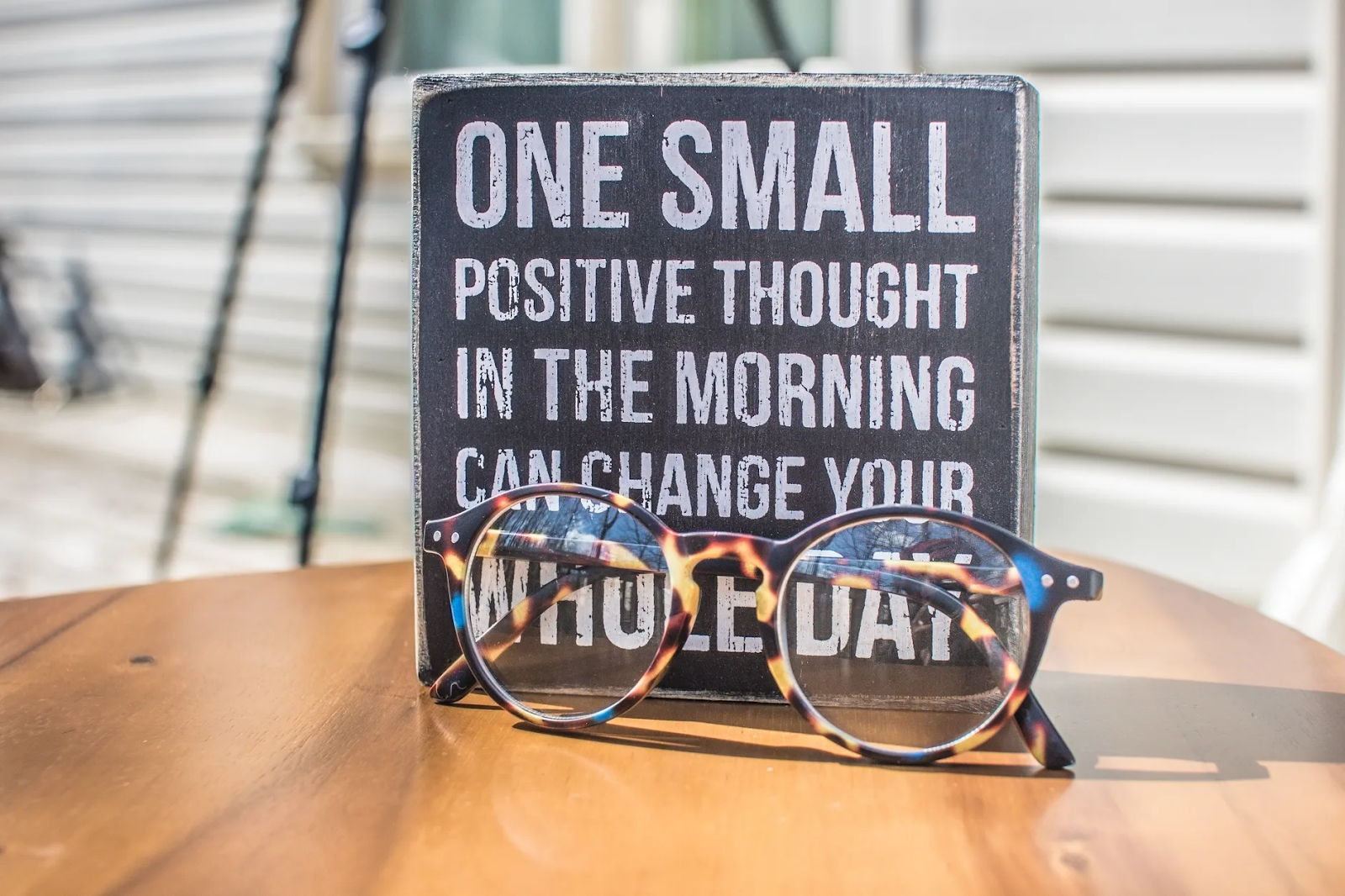 """A sign standing on a table has the words """"One Small Positive Thought in the Morning Can Change Your Whole Day."""" A pair of glasses rests in front of it"""