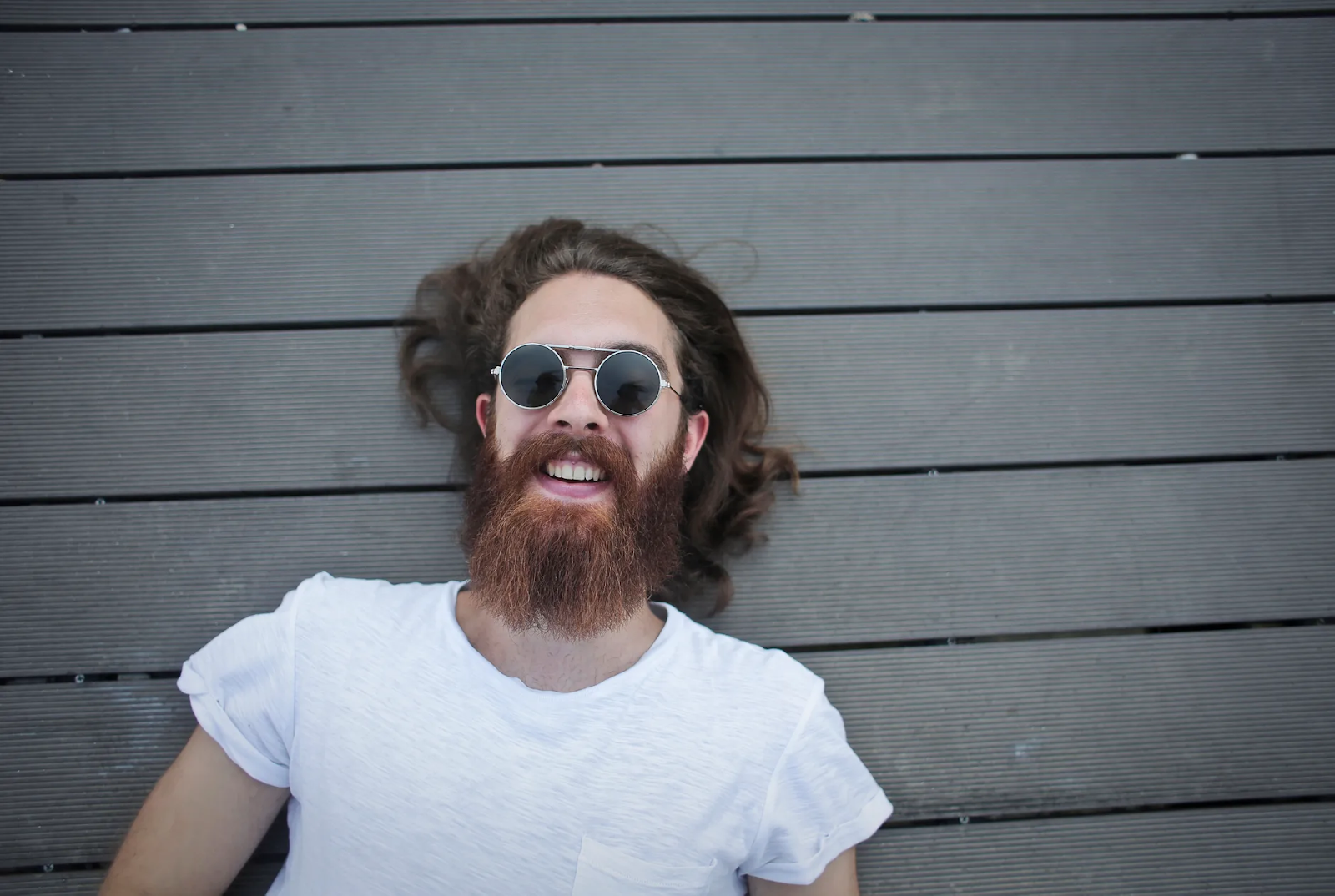A bearded man wearing sunglasses laughs up at the sky as he lies across gray wooden planks