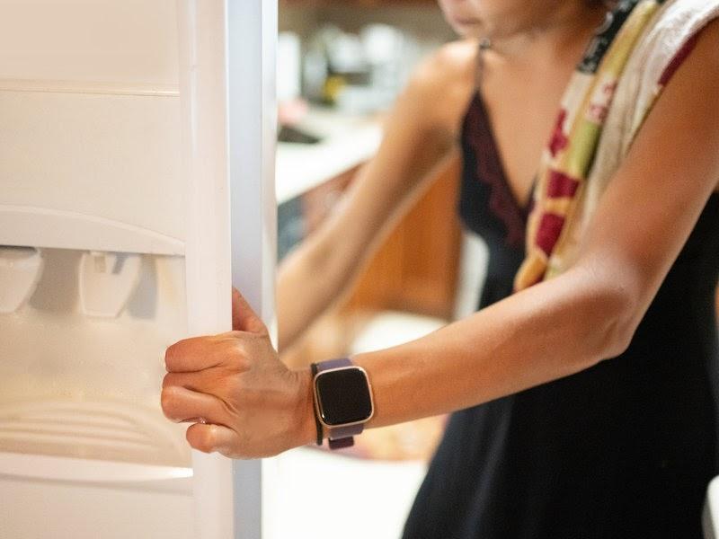 A woman opening a refridgerator door.