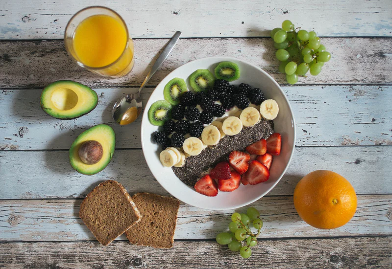 An image depicting a bowl of fruit and granola on a table, along with orange juice, an avocado, bread, and grapes.
