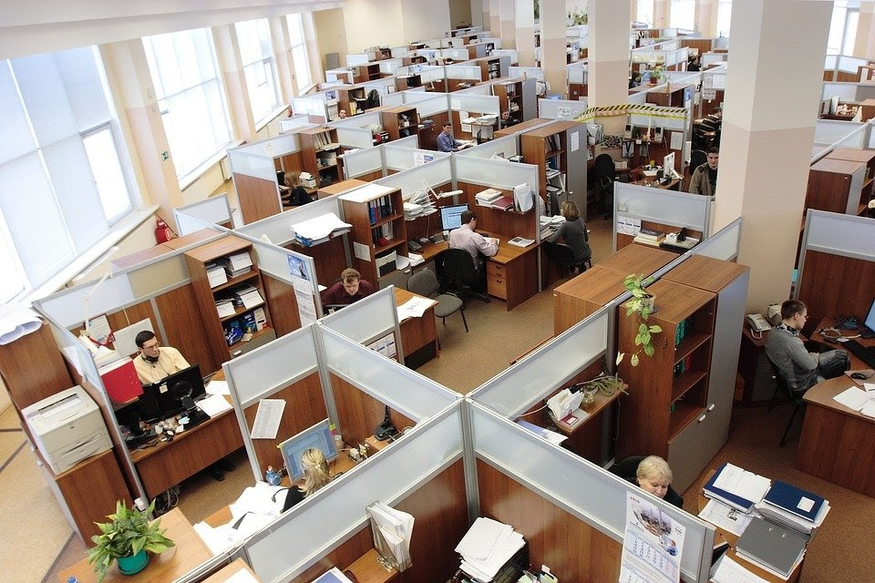 An image depicting an office space, full of cubicles and people at work.