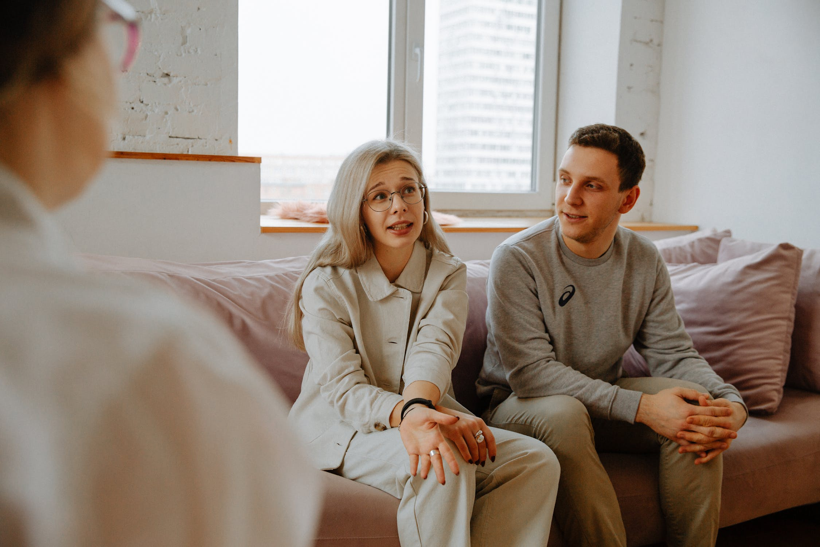 An image of a couple sitting on a couch, speaking to a couples therapist whose profile is visible.