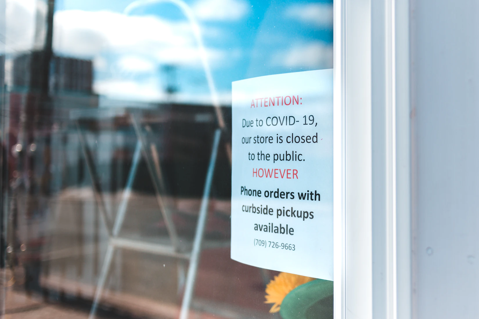 """An image of a flyer in a store window that reads """"Attention: due to COVID-19, our store is closed to the public. HOWEVER, phone orders with curbside pickups available."""""""