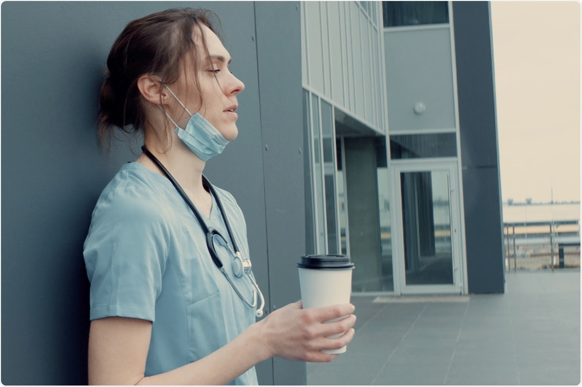 A healthcare worker standing outside of a building holding a cup of coffee.